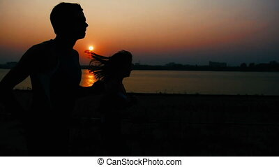 Couple of young adult athletes: woman and man running along promenade of river at sunset, silhouette, slow-motion