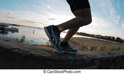 The legs of a runner running in park at sunset, close-up, slow-motion