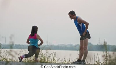 Couple stretching together in the park at dusk, over the river