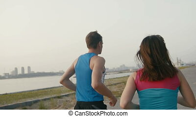Couple of young adult athletes: woman and man running along promenade of river in modern city. Healthy lifestyle concept, rear view