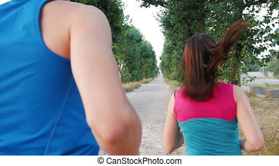 Running sport athletes woman and man jogging on promenade . Healthy lifestyle concept, slow-motion