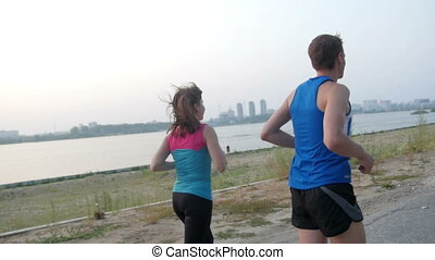 Couple of young adult athletes: woman and man running along promenade of river in modern city. Healthy lifestyle concept, slow-motion, rear view
