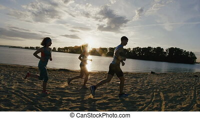 A group of athletes - two girls and a guy runs on beach, near river at sunset