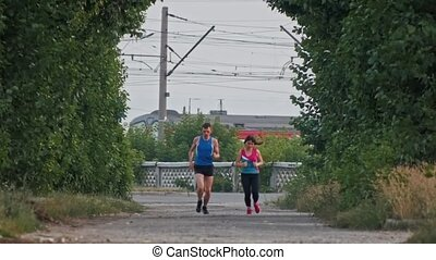 Running athletic couple runners training in park, over the train