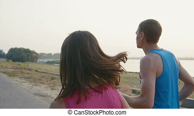 Couple of young adult athletes: woman and man running along promenade of river at sunset. Healthy lifestyle concept, rear view