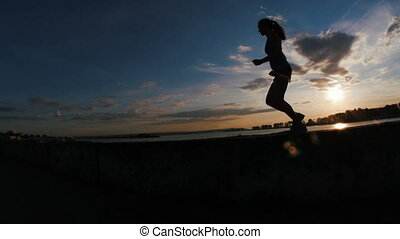 Running young woman with curly hair in park at sunset,...