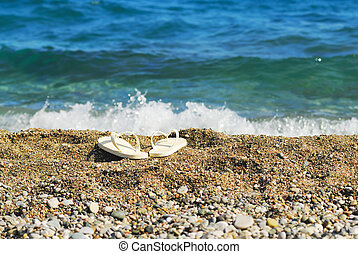 Sand, blue sea and white slippers. Focus on slippers - Sand,...