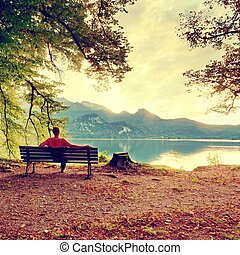 Man sit on wooden bench at mountain lake. Bank under beeches...