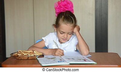 Seven-year girl schoolgirl doing homework distracted and looked into the frame