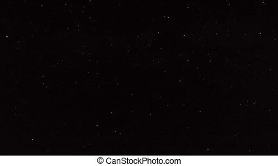 Night time lapse stars passing over mountains and distant...