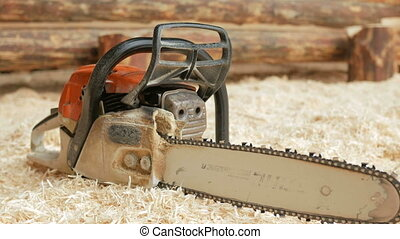 Chainsaw builder at the site of construction of a wooden house. Many sawdust and a part of the future of the house in the background. Close-up and moving camera