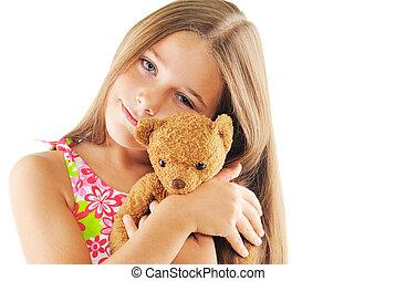 Little girl hugging bear toy