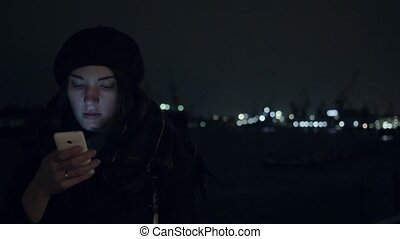 Pretty young woman smiling, using her smartphone. Night city cold weather cold tone shot