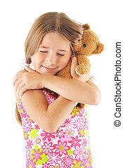 Little girl hugging bear toy. On white background