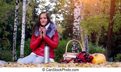 Young cold woman sitting on picnic drinking hot tea from a...