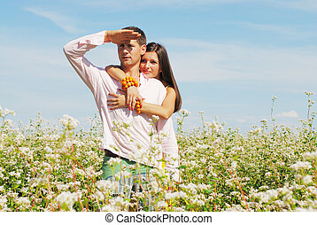Young couple on field of flowers in sunny day