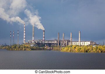 smoke from the chimney of power plant on a river bridge