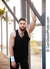 Handsome bearded sportsman in sportswear and wristband...