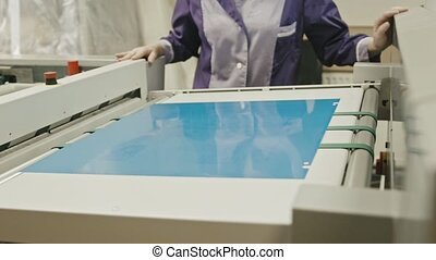 industrial printing process - worker monitors the printing...