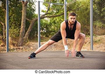 Attractive young male athlete stretching his legs outdoors