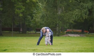 Happy family: Father, Mother and child - little girl walking in autumn park: dad holding daughter