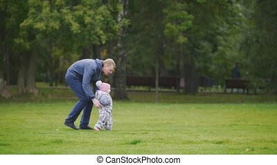 Happy family: Father, Mother and child - little girl walking in autumn park: dad going to the daughter