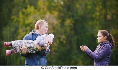 Happy family: Father, Mother and child - little girl walking in autumn park: playing and clapping hands, slow motion