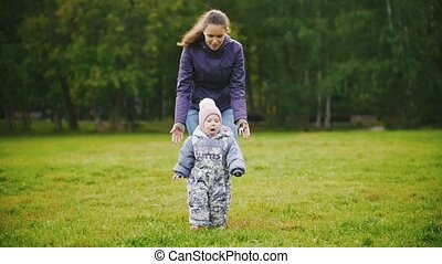 Happy family: Mother and child - little girl walking in autumn park: baby playing at the grass, slow motion