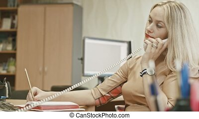 Attractive young woman speaking telephon in office - manager at work, close up