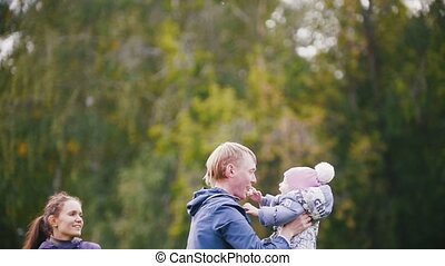 Happy family: Father, Mother and child - little girl walking in autumn park: dad and daughter, slow motion