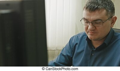 Stuff in office: man in glasses working at computer, close...