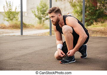 Side view of a sports man athlete ties his shoelaces...