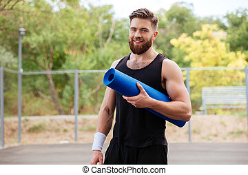 Smiling cheerful fitness man with yoga mat standing outdoors