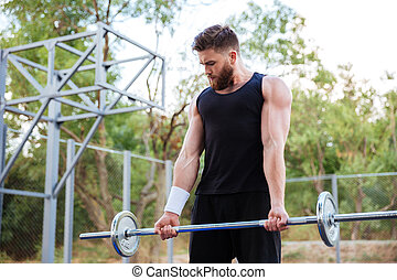 Confident young fitness man doing exercises with barbell