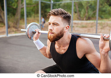Concentrated bearded sports man doing squatting exercises...