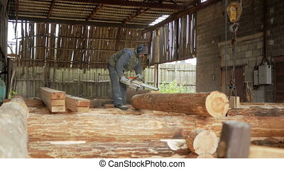 Man cuts wood chainsaw for future home. Protective face mask on the face of the builder and a lot of sawdust. Hangar with a part of the future home on the background