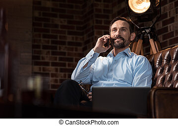 Positive nice businessman holding a smartphone - Making a...