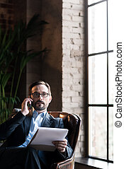 Serious smart businessman working in his study - Focused on...