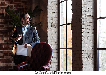 Handsome stylish businessman looking into the window - View...