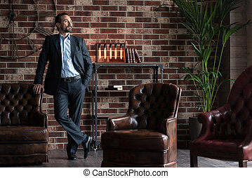 Handsome successful businessman standing in his study room -...