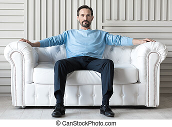 Confident handsome man sitting on a sofa - Like a boss....