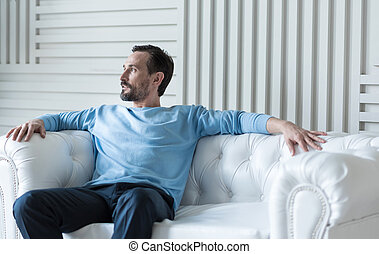 Good looking attractive man reclining on the sofa - Having a...