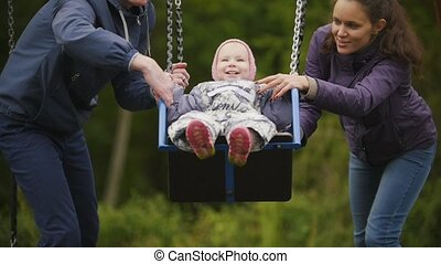 Young happy family at playground - dad, mother and baby daughter - children's swing, slow motion, close up