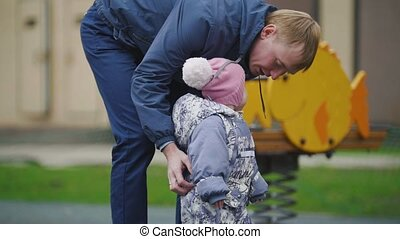 Happy family: Father, Mother and child - little girl walking in autumn park: dad and baby playing at playground