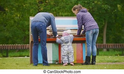 Happy family: Father, Mother and child - little girl walking in autumn park: playing near piano