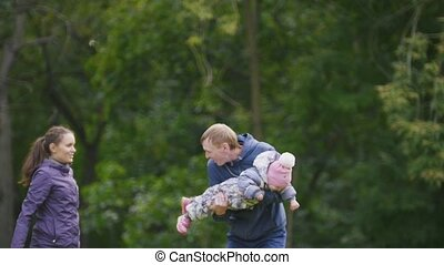 Happy family: Father, Mother and child - little girl walking in autumn park: playing outdoor