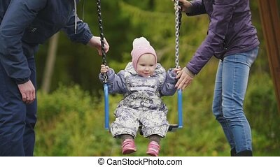 Young happy family at playground - dad, mother and laughing baby daughter - children's swing, slow motion