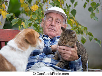 Senior man with pets - Senior man sitting on bench in...