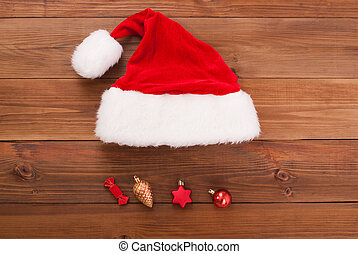 Santa hat with toys on wooden background.