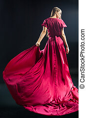 Back view of young blonde woman in bright pink dress -...
